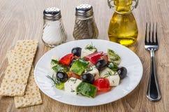 Grekisk sallad i plattan, grönsakolja som är salt, peppar, knäckebröd Royaltyfria Bilder