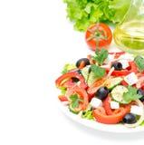 Grekisk sallad med fetaost, oliv och grönsaker på en vit Royaltyfri Bild