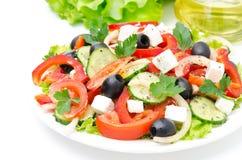 Grekisk sallad med fetaost, oliv och grönsaker på vit Royaltyfri Foto