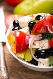 Grekisk sallad med nya grönsaker, fetaost och svarta oliv close upp Fotografering för Bildbyråer