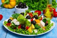Grekisk sallad med nya grönsaker, fetaost och svarta oliv på en träbakgrund Arkivfoto