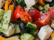 Grekisk sallad med tomater, gurkor, spanska peppar, fetaost, oliv och lökar arkivfoto