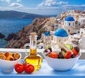 Grekisk sallad mot berömd kyrka i den Oia byn, Santorini ö i Grekland royaltyfria bilder
