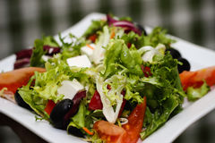 Grekisk sallad på en vit platta royaltyfri foto