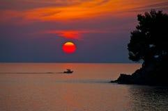 Grekisk solnedgång med ett fartyg Arkivbilder