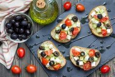 Grekisk stilcrostini med fetaost, tomater, gurkan, oliv och örter fotografering för bildbyråer