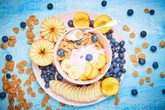 Grekisk yoghurt för bär med den frefhblåbär, bananen och flingor i den rosa bunken på den blåa trätabellen Fotografering för Bildbyråer