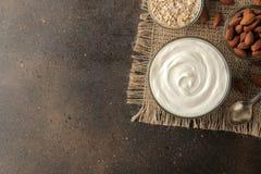 Grekisk yoghurt i en exponeringsglasbunke bredvid en sked, en havremjöl och mandlar på en mörk bakgrund sund mat Naturlig yoghurt royaltyfria bilder