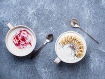 Grekisk yoghurt två med driftstopp, chiafrö och bananen i den vita bunkenollan royaltyfri foto