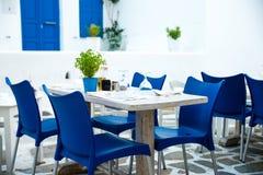 Grekiska örestauranger med färgrika tabeller Arkivbild