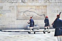 Grekiska evzones - grekiska tsolias - som framme bevakar den presidents- herrgården av gravvalvet av den okända soldaten Arkivfoto