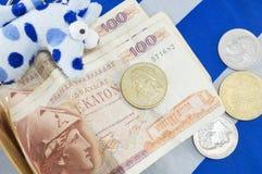 Grekiska gamla valutadrakmasedlar på den grekiska flaggan Arkivfoto