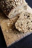 Grekiskt Hel-vete brunt bröd på brödbräde Arkivfoto