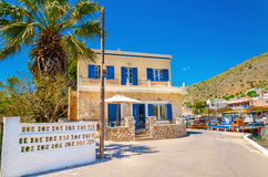 Grekiskt hus med blåa träfönster, Grekland Royaltyfria Foton