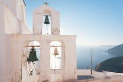 Grekiskt vitt kyrkligt torn på Santorini med klockor och havet Royaltyfri Fotografi
