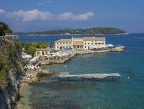 Grekland Korfu, Kerkyra stad, september 26, 2018: Den Faliraki stranden Alecos badar den offentliga badningfläcken med vaggar och arkivfoto