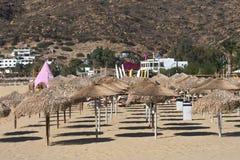 Grekland ?n av Ios Solsängar och slags solskydd på den Mylopotos stranden royaltyfria foton
