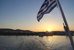 Grekland Paros, grekisk flagga på solnedgången på färjan royaltyfri fotografi