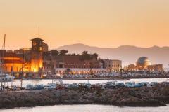 Grekland, Rhodes - Juli 13 Mandraki invallning och port på solnedgången på Juli 13, 2014 i Rhodes, Grekland Royaltyfri Bild