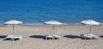 Grekland sätta på land paraplyer för orangen för kos för kefalos för den stolsgreece ön Kefalos strand Stolar och paraplyer Arkivbild