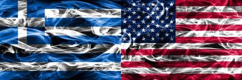 Grekland vs Amerikas förenta stater röker den flaggor förlade sidan vid si arkivbilder