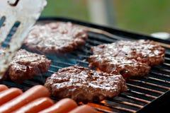 Grelhando hamburgueres e cães quentes Fotos de Stock