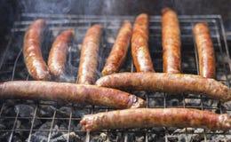 Grelhando salsichas em uma grade do carvão vegetal barbecue Foto de Stock Royalty Free