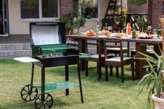 Grelhe com os carvões que estão no gramado verde e na tabela servida com pratos e bebidas atrás fotos de stock royalty free