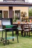 Grelhe com os carvões que estão no gramado verde e na tabela servida com pratos e bebidas atrás fotografia de stock