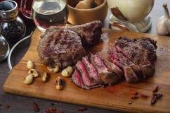 Grelhe a composição do bife do olho do reforço da carne no fundo de madeira Imagens de Stock