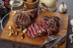 Grelhe a composição do bife do olho do reforço da carne no fundo de madeira Fotos de Stock