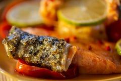 Grelhou um salmão e um limão Dourado fritado uma pele dos peixes em um tomate Fundo obscuro fotos de stock royalty free