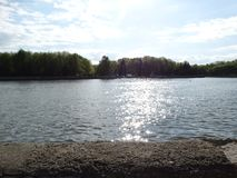 Greller Glanz des Sonnenlichts im Fluss Svisloch lizenzfreie stockfotografie