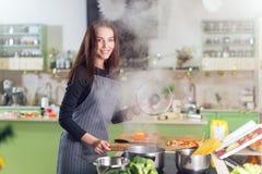 Grembiule d'uso della giovane donna graziosa che fa cena che cucina gli spaghetti dopo la ricetta in un libro che sta nella cucin fotografie stock libere da diritti
