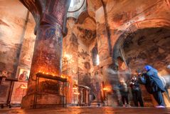 Beautiful interior of Church of the Archangels with columns, frescoes and some people praying. GREMI, GEORGIA - OCT 1: Beautiful interior of Church of the royalty free stock images