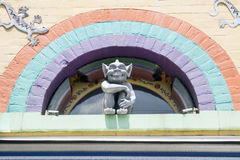 Gremlin Sitting in Arch. Gray Gremlin with Pointy Ears Giving an Evil Smile While Sitting in Front of an Arched Window that is Outlined with a Purple Blue and stock photos