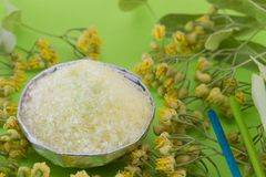 Gren bath salt on with linden flowers on a green backgound Stock Photos