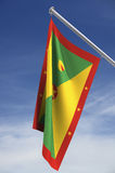 Grenada Flag. With clipping path, against a blue sky with clouds vector illustration