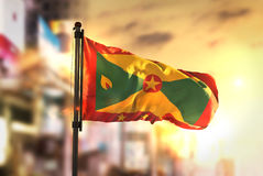 Grenada Flag Against City Blurred Background At Sunrise Backligh Royalty Free Stock Photography
