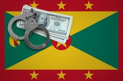 Grenada flag with handcuffs and a bundle of dollars. The concept of breaking the law and thieves crimes stock image