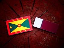 Grenada flag with Qatari flag on a tree stump isolated Stock Photography