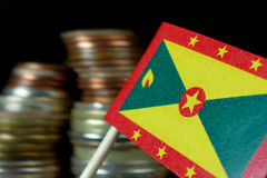 Grenada flag waving with stack of money coins Royalty Free Stock Images