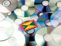 Grenada flaga na górze cd i DVD stosu odizolowywającego na bielu Obrazy Stock