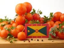 Grenada-Flagge auf einer Holzverkleidung mit den Tomaten lokalisiert auf einem Weiß Lizenzfreies Stockfoto