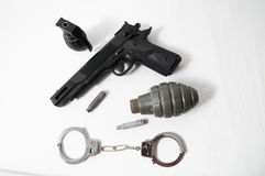 Grenade Bullets Gun and Handcuffs Royalty Free Stock Images