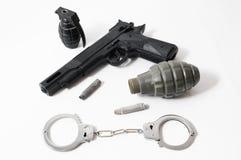 Grenade Bullets Gun and Handcuffs Royalty Free Stock Photos