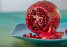 Grenade et graines rouges de fruit d'un plat bleu Beau fruit tropical lumineux images libres de droits