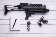 Grenade launcher with shell casings, notepad and pen,compass.Top. Hand grenade launcher,shell casings, notepad ,pen,compass on white wooden table .Top view stock image