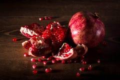 Grenade rouge juteuse avec des graines sur la table en bois Photos libres de droits