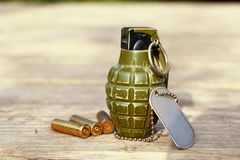 Grenade with shells and dog tag. Military hand grenade next to gun shells and dog tag royalty free stock photo